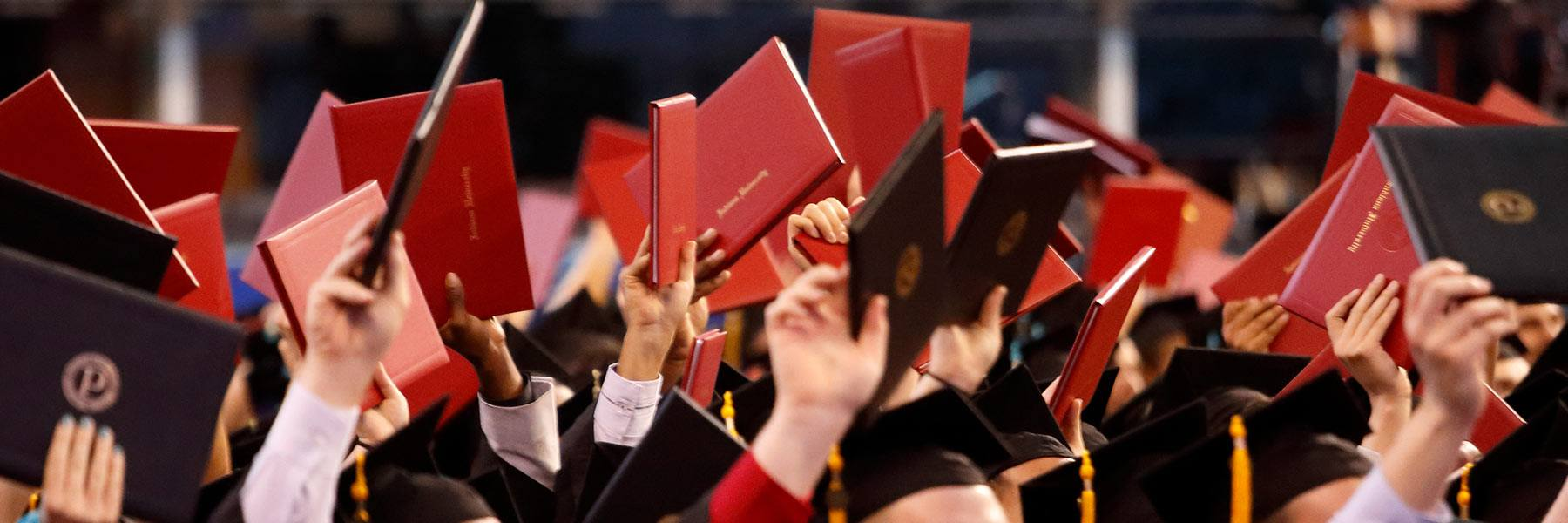 Students raise their diplomas at Commencement.