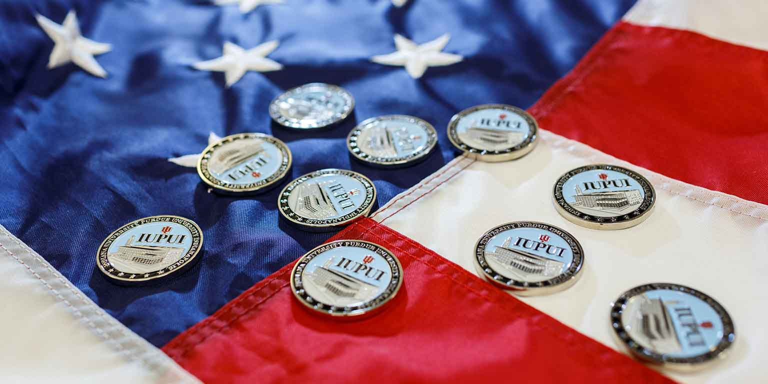 IUPUI medallions lie on an American flag.